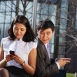 Business couple sitting on the bench chatting with mobile phone - Stock Photo