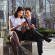 Business couple sitting on the bench chatting with mobile phone — Stock Photo #20666247