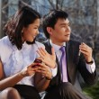 Stock Photo: Business couple sitting on bench chatting with mobile phone