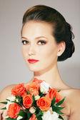 Beautiful bride with stylish make-up and hairdo holding bouquet — Stock Photo