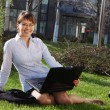 Woman lying on grass with laptop with business building on back — Stock Photo