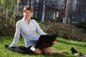 Woman lying on grass with laptop mit geschäftshaus auf rückseite — Stockfoto