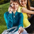 The beautiful girl with girlfriend and talking with cellphone — Stock Photo