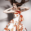 Stock Photo: Young beautiful asibrunette in gorgeous dress, motion shot
