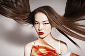 Photo of beautiful asian woman with magnificent hair. Fashion Kravets dress. — Stock Photo