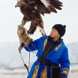 NURA, KAZAKHSTAN - FEBRUARY 23: Eagle on kid's hand in Nura near Almaty on February 23, 2013 in Nura, Kazakhstan. The traditional event happens yearly and the place becomes as a medieval times city. — Stock Photo