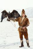 NURA, KAZAKHSTAN - FEBRUARY 23: Eagle on kid's hand in Nura near — Stock Photo