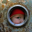 Stock Photo: Kid looking through the round window