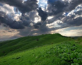 Wide panoramic view to green hills and dramatic sky — Stock Photo