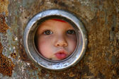 Kid looking through the round window — Stock Photo