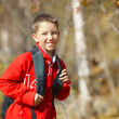 Happy smiling hiker boy with backpack in forest. Dressed in red — Stock Photo
