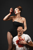 Vampire woman eating man heart — Stock Photo