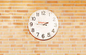 An old station clock over bricks wall — Stock Photo