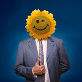 Smiling sunflower head man in suit coat with present thumbs up o — Stock Photo