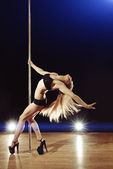 Young sexy pole dance woman with fluttering hair performing on s — Стоковое фото