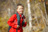 Happy smiling hiker boy with backpack in forest. Dressed in red  — Stock fotografie