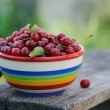 Fresh cherries in color plate on wooden table in the garden — Stock Photo