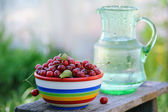 Jug of cold fresh water with cherries on wooden table in the garden — Stock Photo