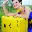 Beautiful smiling girl in a blue dress with a yellow suitcase on the road — Stock Photo