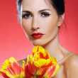 Pretty woman holding a bunch of tulips on red background — Stock Photo