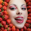 Royalty-Free Stock Photo: Young beautiful woman with white teeth enjoying strawberries and looking into the camera