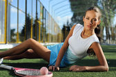 Athletic healthy girl lying on the grass and resting after tennis outdoors — Stok fotoğraf