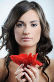 Beautiful woman with fresh health skin of face and red flower in hand — Stock Photo