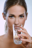 Healthy sport woman drinks cold mineral water from glass — Stock Photo