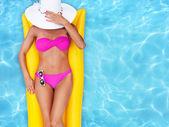 Girl sunbathing in a pool — Stock Photo
