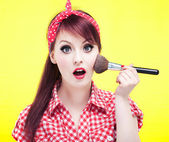 Cute pin up girl applying blusher — Stock Photo