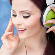 Portrait of a young woman listening to music with headphones — Stock Photo #13407741