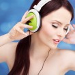 Portrait of a young woman listening to music with headphones — Stock Photo #13407759