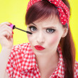 Funny portrait of girl applying mascara - Stock Photo