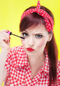 Funny portrait of girl applying mascara — Stock Photo