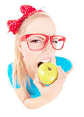 Funny girl biting an apple isolated on white, fish eye shot — Stock Photo