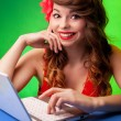 Colorful portrait of smiling young woman working on a laptop — Stock Photo