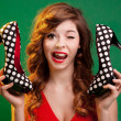 Funny young woman holding high heels shoes — Stockfoto