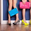 Two girls wearing high heels waiting at the door - Stockfoto