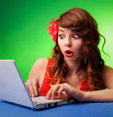 Surprised young woman at a computer — Stock Photo