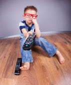 Cheerful child with tv remote control — Stock Photo