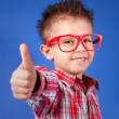 Cheerful five years old boy with thumb up - Stock Photo