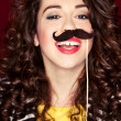 Royalty-Free Stock Photo: Attractive playful young woman holding mustache on a stick