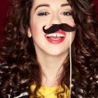 Stock Photo: Attractive playful young womholding mustache on stick