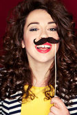 Attractive playful young woman holding mustache on a stick — Stok fotoğraf