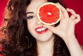 Portrait of pretty woman holding grapefruit — Stock Photo