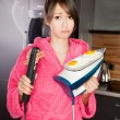 Beautiful young woman frying eggs and bacon on an iron and hair straightener — Stock Photo