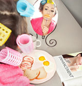Woman with sausages on a fork simulating lip enhancement while having breakfast — Stock Photo