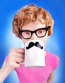 Nerdy boy holds a cup with fake mustaches — Stock Photo