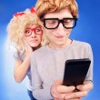 Stock Photo: Girl is spying on boyfriend he is using a smart phone