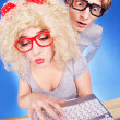 Funny guy is spying on girlfriend she is using laptop computer — Stock Photo #24813849